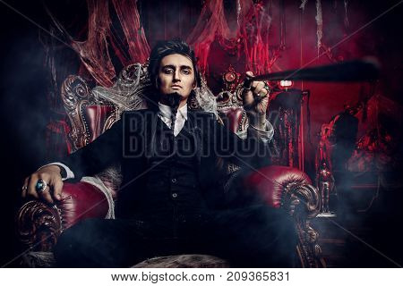 Halloween. Mysterious gloomy man in a black tailcoat in an old abandoned castle. The Dark Lord. Vampire man.