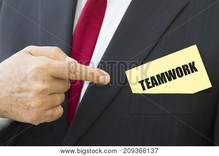 Businessman showing a card with text TEAMWORK.