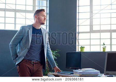 Focused young businessman wearing a blazer leaning on his desk looking deep in thought while standing alone in a large modern office