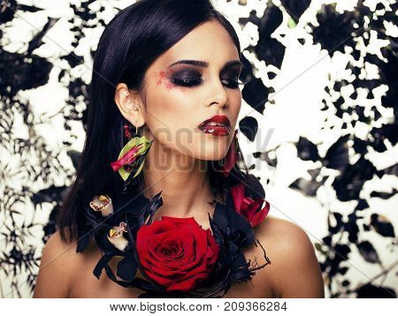 pretty brunette woman with rose jewelry, black and red, bright make up kike a vampire closeup red lips, halloween concept