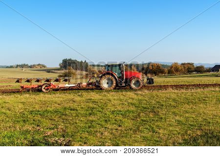 Red tractor pole field. Autumn field work. Life on the farm. Agricultural landscape in the Czech Republic