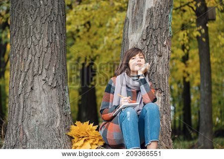 Wonderful autumnal view. Charming young happy smiling woman sitting on the grass in a park, take notes in notebook. Takes notes in a notebook. Artist girl painting sitting on the wood.