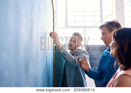 Focused group of work colleagues brainstorming together on a chalkboard while standing in a meeting room of a modern office
