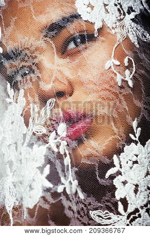 portrait of beauty young afro asian woman through white lace, like new bride under veil close up