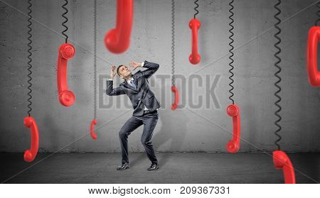 A scared businessman on concrete background hides from many red retro phone receivers hanging down on their cords. Business communications. Customers support. Always on phone.