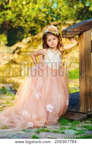 Pretty little girl wearing beautiful dress stands in a summer park. Children's fashion. Birthday.