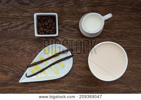 Vanilla, coffee beans, milk and coffee. Vanilla coffee on wooden table. Winter hot drink.
