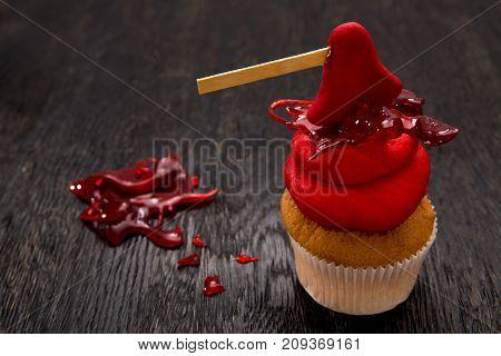 Halloween red one cupcake with ax. Cupcake with blood. Halloween decorated cookie on dark wooden table. Close up