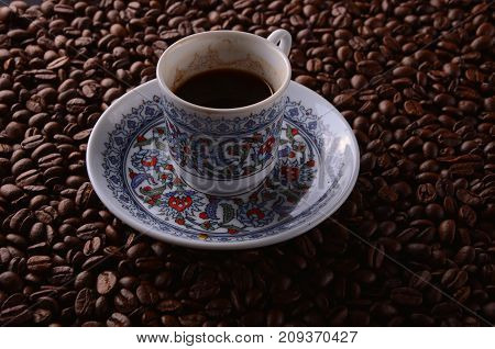 Traditional Hot Coffee Cup With Beans  Over A Black Background.
