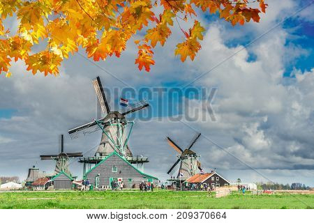 traditional Dutch scenery with windmill of Zaanse Schans with dramatic cloud sky, Netherlands at autumn day