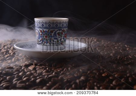 Traditional Hot Coffee Cup With Beans And Smoke Steam Over A Black Background.