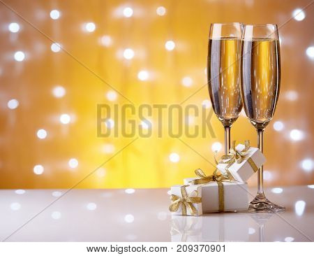 Two glasses with champange and gift boxes on a yellow background with lights of garland.