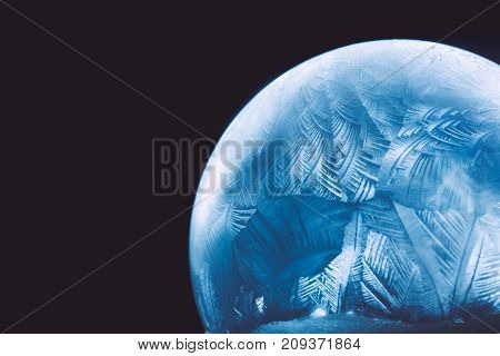 Frozen snow globe christmas magic ball with flying snowflakes. Winter Background. For Christmas and New Year Holidays precious backdrop. Ice patterns frosted on ball of soap against dark black abstract bokeh background.
