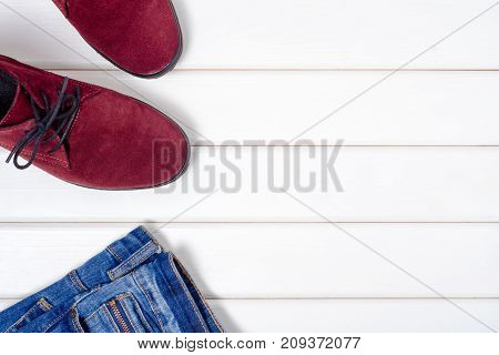 Female suede shoes jeans on a white wooden background