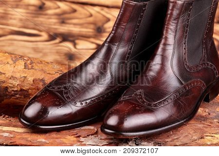 Brown Leather Chelsea Boots Polished On Pine Board. Waxing Boots.copy Space.closeup