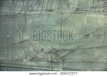 Damaged, broken glass sheet with black cracks on green background