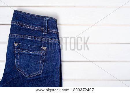 Blue jeans on a white wooden background2