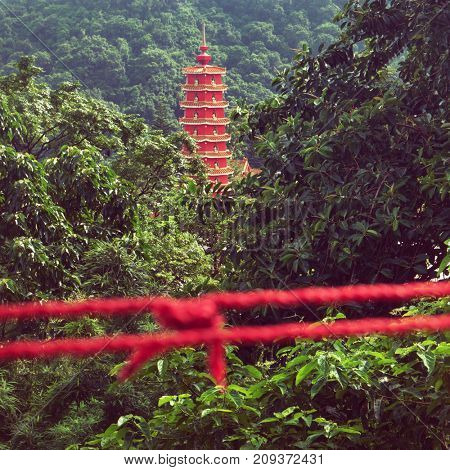 Hong Kong - October 2017: Pagoda surrounded by lush greenery with red rope in foreground. Ten Thousand Buddhas Monastery