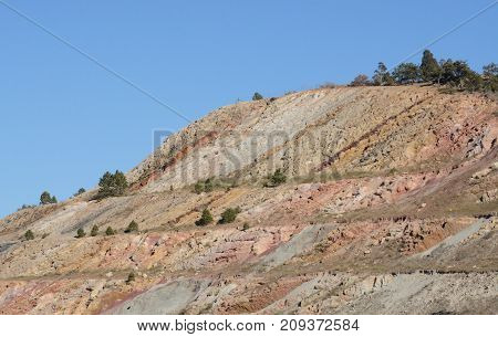 Geological layers of mountain revealed from cutting away part of mountain to make path for Colorado interstate highway 70