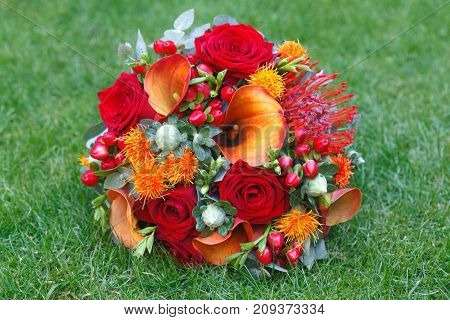 Red and orange bouquet isolated on green grass background