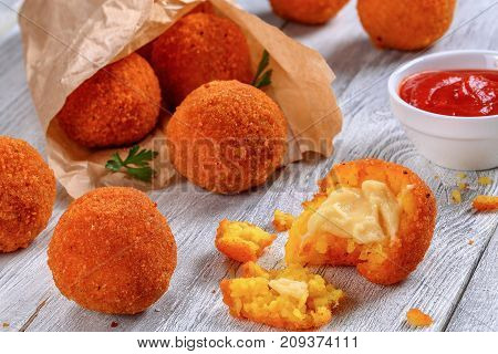 Rice Balls Stuffed With Cheese In Paper Cornet
