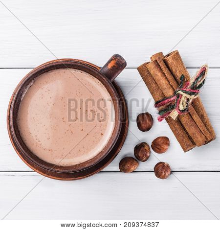 Hot cocoa with milk in brown clay cup hazelnut and cinnamon sticks on table of white wooden planks top view.
