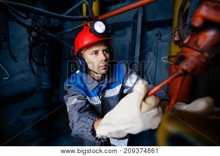 young coal miner is underground in a mine for coal mining in overalls against the backdrop of mining equipment. concept of repair of industrial equipment.