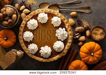 Sweet pumpkin pie decorated with whipped cream overhead shot with copy space