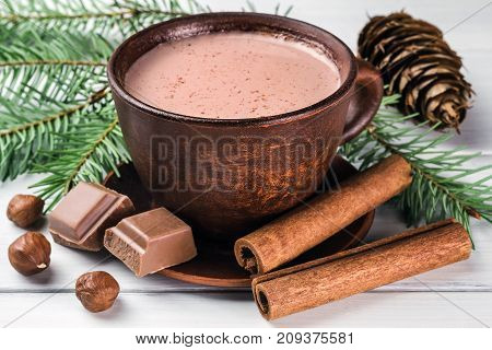 Christmas cup of hot cocoa with milk broken chocolate cubes hazelnut and cinnamon sticks christmas tree branches pine cone on white wooden planks.