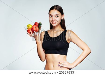 a young sundry girl watches her figure, holds a plate with useful vegetables and fruits