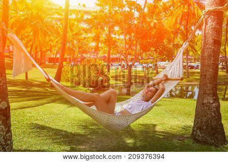 beautiful girl resting in a hammock at sunset. Toned