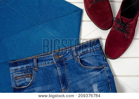 Female suede shoes sweater jeans on a white wooden background