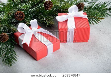 Two christmas gift boxes with bows on a light-blue stone background copy space