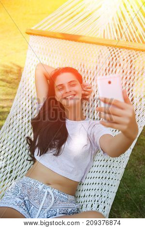 Relaxed Young Woman Looking At Mobile Phone In Hammock. Toned