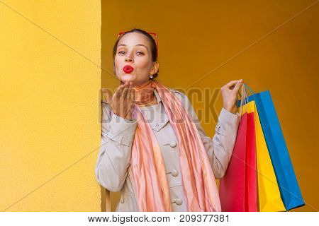 The Beautiful Woman  With Red Lips, Send Kiss For You And Holding Shopping Bags. Isolated Studio Sho