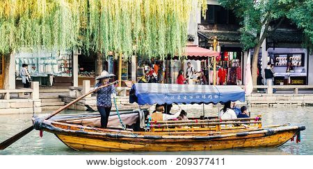 Suzhou, China - Nov 5, 2016: Boat with tourists cruising by at the historic Zhouzhuang Water Town.