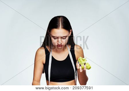the girl in a sport short shirt is eating cabbage and looking down, sports body, delicious healthy food