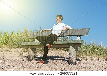 young man sitting on bench in sun beam