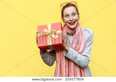 Young Adult Woman Holding Gift Box And Looking At Camera And Toothy Smile.