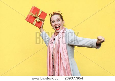 Catch Your Gift! Young Adult Crazy Woman Swung And Wants To Throw Off Your Gift Box, Isolated On Yel