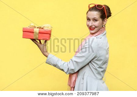 Gift With Love. Interesting Ginger Young Adult Woman Standing Profile With A Gift Box On Yellow Back