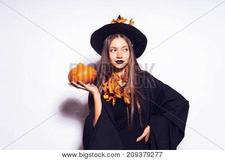 young  girl with black lipstick in the form of a witch for halloween, her black cloak fluttering, holding a pumpkin in her hands