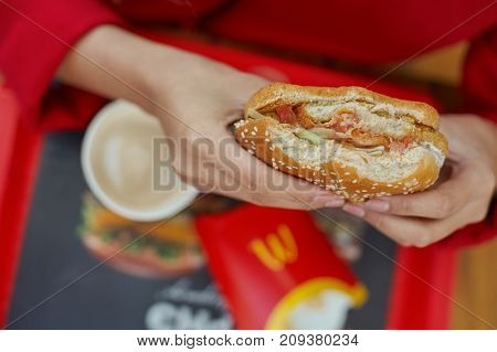 KALININGRAD, RUSSIA - CIRCA OCTOBER, 2017: woman hands hold hamburger at McDonald's restaurant.