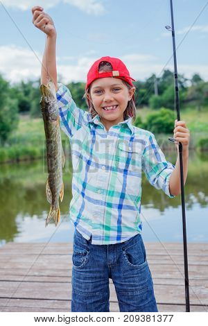 Happy cute boy enjoyed the fishing. Holding a big pike.