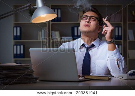 Businessman under stress smoking in office