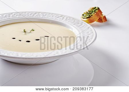 plate with creamy potato soup with basil drops