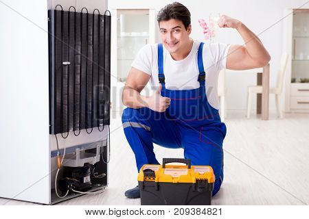 Repairman contractor repairing fridge in DIY concept