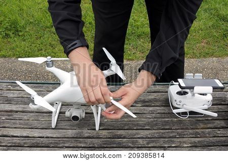 Unrecognizable person prepares a drone for a flight. Real people. Copy space