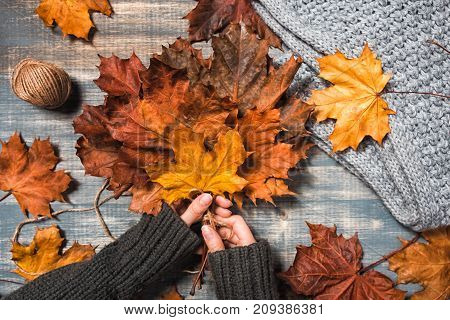 Workspace with yellow and red maple leaves. Desktop with laptop fallen leaves on grey wooden background. Flat lay top view. Woman hands