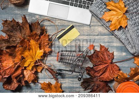 Shopping cart on wooden Desktop. Workspace with laptop maple yellow and red leaves credit card on grey wooden background. Flat lay top view.